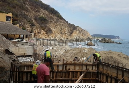 Laborers construct a seawall in Latin America to protect a small beachfront town against increasingly severe storms