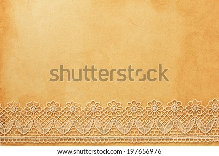 Lace on old grunge paper - stock photo