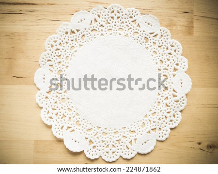Lace paper on wooden table background - stock photo