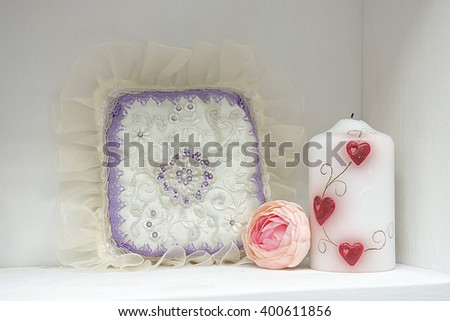lace pillow, peony and the candle, standing on a white table - stock photo