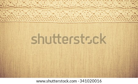 Lace ribbon on natural linen, bright cloth fabric background. Border frame. vintage style
