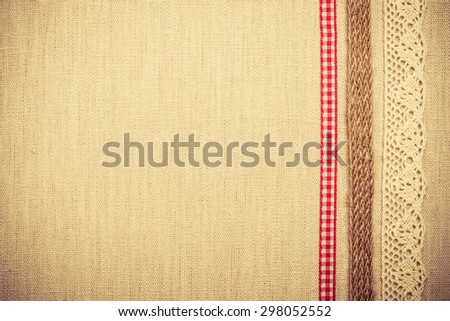Lace, rope and red ribbon frame on natural linen, bright cloth fabric background. Retro vintage style - stock photo