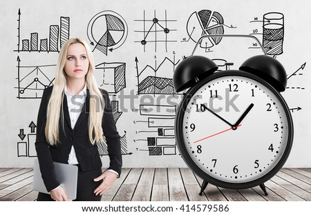 Lack of time concept with thoughtful businesswoman, huge alarm clock on wooden floor and concrete wall with business sketches in the background - stock photo