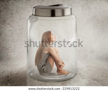 Lack, violation of human rights liberty. Young lonely woman sitting in glass jar isolated grey wall background. Suppression of freedom, restrain, employee working conditions, life limitation concept - stock photo