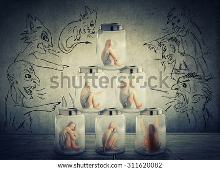 Lack, violation of human rights. Young lonely woman sitting in a pile of glass jars surrounded by angry negative evil men people. Suppression of freedom restrain working conditions, life limitation - stock photo