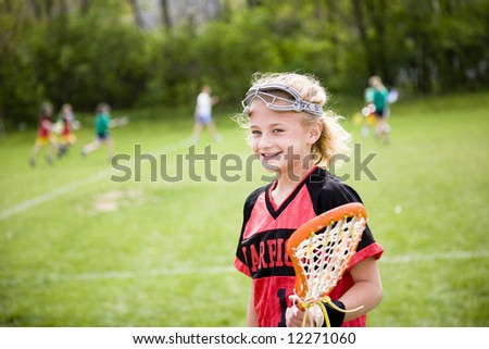 Lacrosse player with the game going on in the background - stock photo