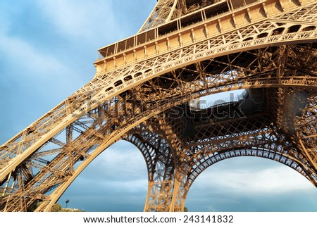 Lacy arches of the Eiffel Tower in Paris, France. Paris is one of the most popular tourist destinations in Europe. - stock photo