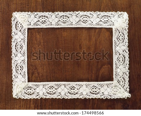 lacy frame on wooden background with space for your text - stock photo