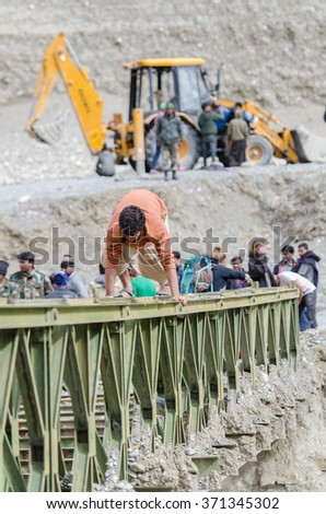 Ladakh,India - July 20,2015 : Travelers climbing broken bridge during flood problem, way to Manali affected by landslide