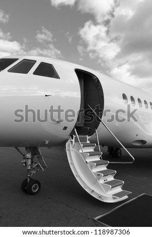 ladder in a private jet and red carpet on ground - stock photo