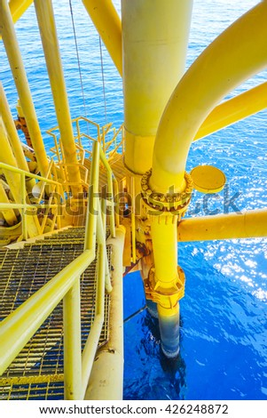 Ladder on Aligned Oil and Gas Pipeline and Production slots on the sea background in Offshore wellhead remote platform, Energy and petroleum industry. (Vertical) - stock photo