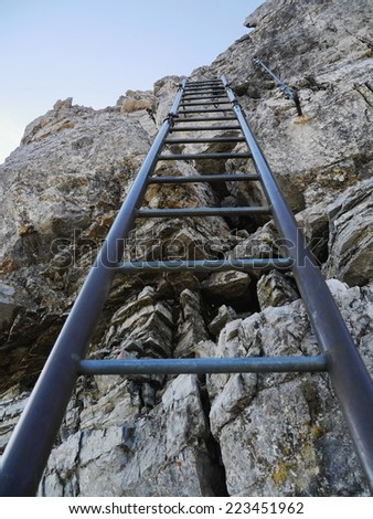 Ladder stair climbing on mountain - stock photo