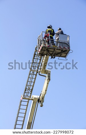 Ladder truck with firefighters and blue sky background - stock photo