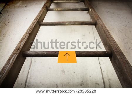 Ladder with a note pointing up - stock photo