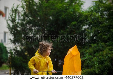 Laddie in a bright yellow raincoat and with an umbrella resists to rushes of strong wind. He hardly holds an umbrella. A fair hair of the boy was disheveled by wind. - stock photo