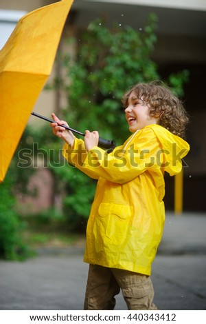 Laddie 8-9 years in a bright yellow raincoat tries to hold an umbrella from windflaws. The boy holds an umbrella with two hands. To him it is cheerful. - stock photo