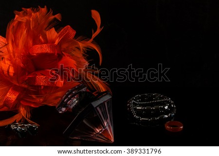 Ladies Feather Flower Party Hair Accessory, Black Stone Bracelet and Earrings, Red Ring and Classy Perfume Bottle. Black Background.