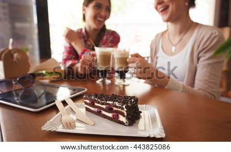 Ladies having round or cheers with cups of latte. Toned image of best friends meeting or date in cafe or restaurant.