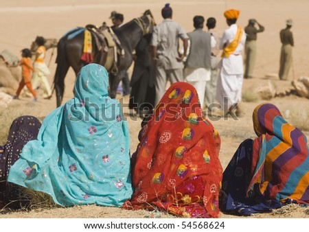 Ladies in brightly colored saris watching events at the Desert Festival in Jaisalmer, Rajasthan, India