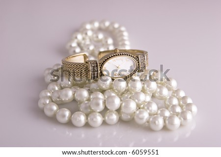 Ladies wristwatch sits atop a pearl necklace on white. - stock photo