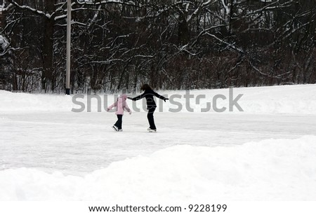 Lady and little girl ice skating - stock photo