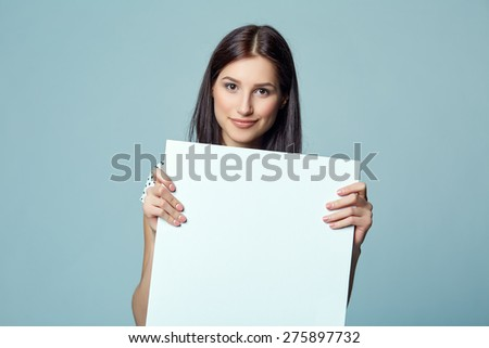 Lady beautiful woman standing behind, holding white blank advertising board banner, on blue background - stock photo