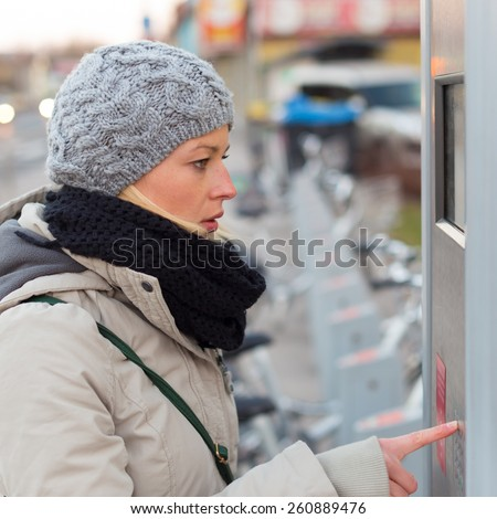 Lady dialing on keyboard of urban bicycle station. Bikes for rent. Green sustainable ecological public transport. Healthy lifestyle. - stock photo