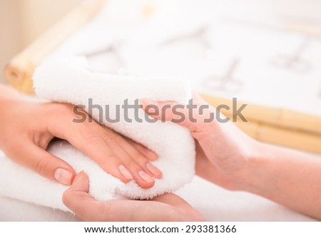 Lady during hand massage in spa, close-up. Female hand resting on white towel. - stock photo