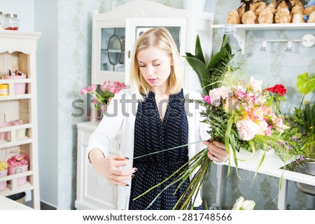 Lady elegantly ties the flowers with tape - stock photo
