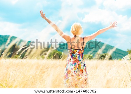 Lady enjoying the nature. Young woman arms raised enjoying the fresh air in summer meadow. - stock photo