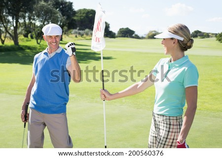 Lady golfer holding eighteenth hole flag for cheering partner on a sunny day at the golf course - stock photo