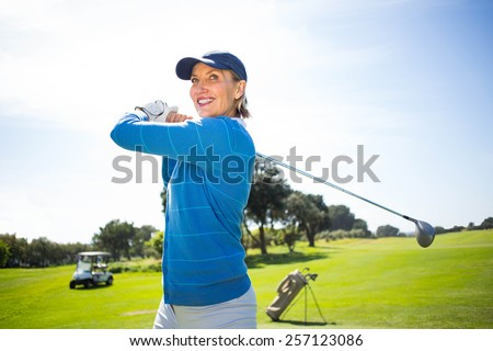 Lady golfer teeing off and smiling on a sunny day at the golf course - stock photo