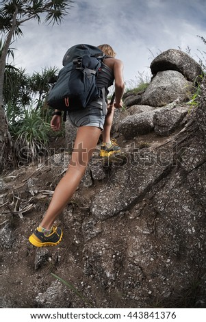 Lady hiker passing rocky terrain - stock photo