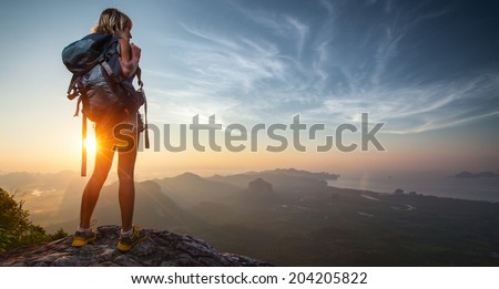 Lady hiker relaxing on top of hill and enjoying sunrise over the valley - stock photo