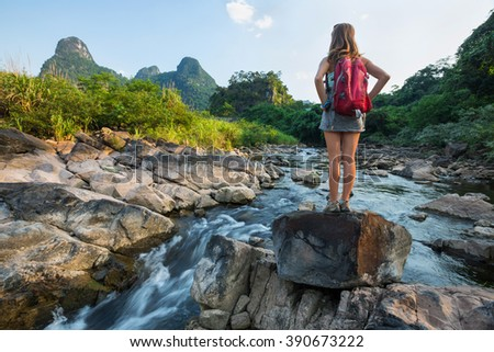 Lady hiker standing on a stone near mountain stream - stock photo