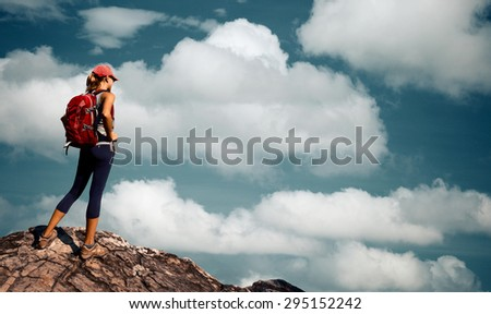 Lady hiker standing on top of the mountain on the sky background full of fluffy clouds - stock photo
