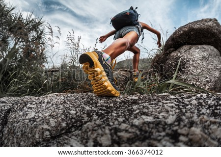 Lady hiker walking through the rocky land. Focus on the foot