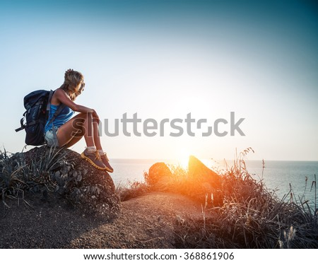 Lady hiker with backpack sitting on the rock and enjoying sunset over the sea