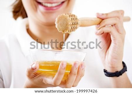 Lady holding a bowl of honey. - stock photo