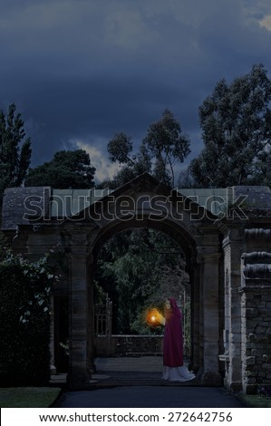 Lady in castle garden at night - stock photo
