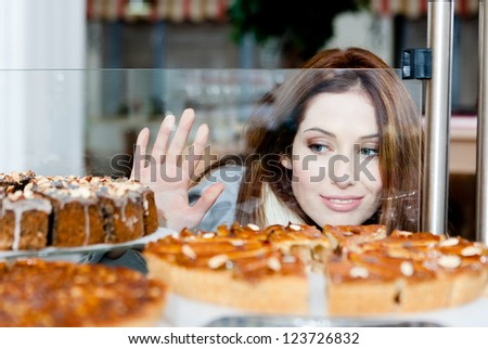 Lady in scarf looking at the bakery window full of different pieces of cakes - stock photo