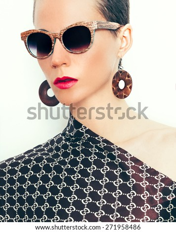 Lady in stylish summer Accessory. Fashion Sunglasses and Earrings. Wooden Style - stock photo