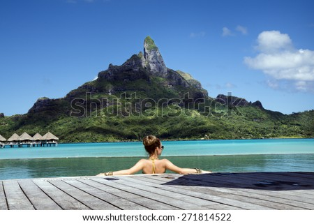 lady in the infinity pool  on the beach of a luxury vacation resort in the lagoon and looking on the Otemanu mountain on the tropical island of Bora Bora, near Tahiti, French Polynesia, Pacific ocean - stock photo