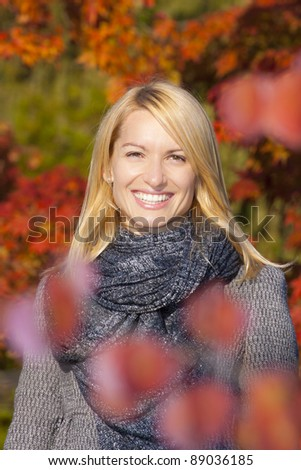 Lady in the park relaxing on the autumn sun. - stock photo