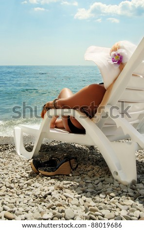 Lady in white hat and bracelets lie on the chaise-lounge at the sea - stock photo