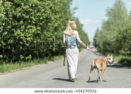Lady is on the road with a dog