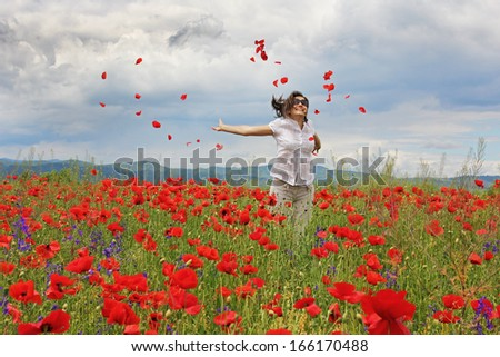 Lady jumping and spreading poppies petals in the air