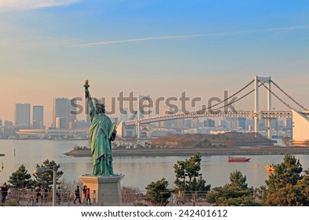 Lady liberty juxtaposed against Rainbow Bridge in Tokyo - stock photo