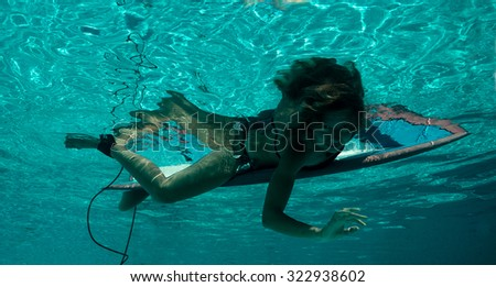Lady lying on the surfboard  - stock photo
