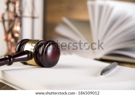 Lady of justice, Wooden & gold gavel and books on wooden table on brown wooden background - stock photo
